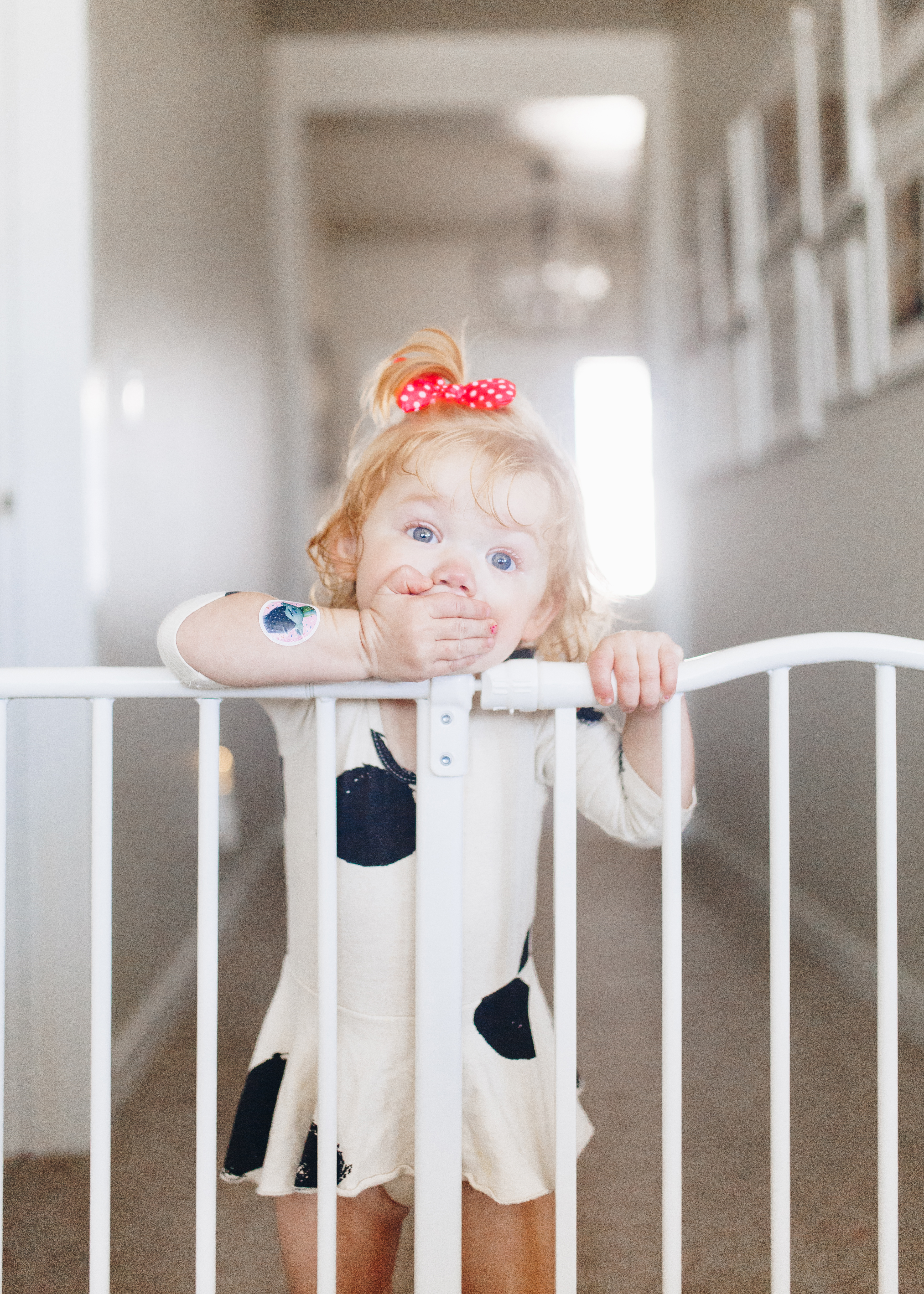 Toddler looking over baby gate