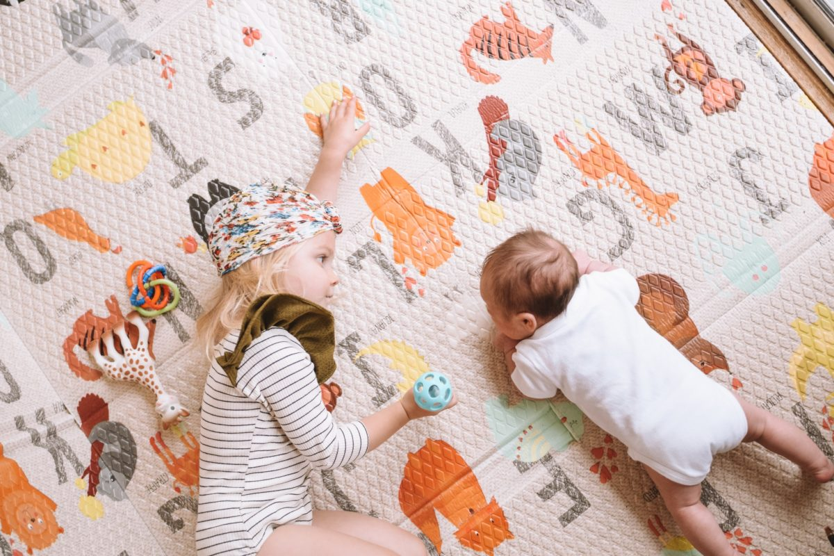 Siblings on ABC Play Mat